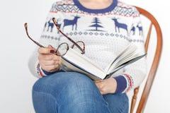 Donna adulta con i vetri che legge un libro Fotografia Stock