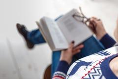 Donna adulta con i vetri che legge un libro Immagini Stock Libere da Diritti