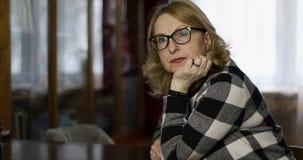 Donna adulta con i vetri che si siedono a casa stock footage