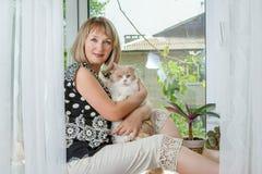 Donna adulta con il gatto sulla finestra Immagini Stock