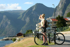 Donna adulta con la bici che esamina le montagne fotografia stock libera da diritti