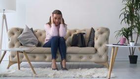 Donna adulta depressa sola che si siede sul sofà a casa stock footage
