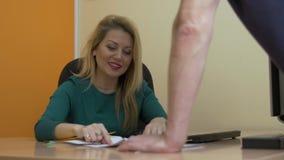 Donna adulta di affari che mostra i documenti per il cliente o il collega nell'ufficio video d archivio