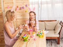 Donna adulta felice con le uova di Pasqua della pittura del bambino Immagini Stock Libere da Diritti