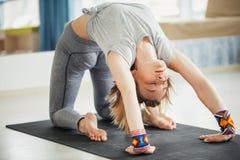 Donna adulta nella posizione di yoga di virasana di supta in studio immagini stock libere da diritti