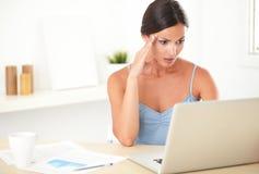 Donna adulta sollecitata che lavora al suo computer Fotografia Stock