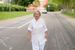 Donna adulta in tutta la camminata bianca alla via Immagine Stock