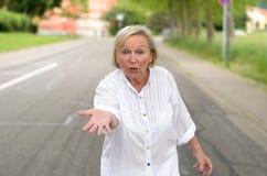 Donna adulta in tutta la camminata bianca alla via Fotografia Stock