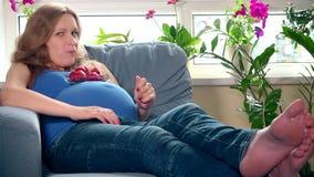 Donna affamata che mangia la bacca e sguardo della fragola alla macchina fotografica con il sorriso video d archivio