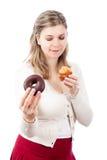 Donna affamata che tiene focaccina e ciambella dolci Fotografia Stock