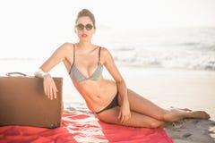 Donna affascinante in bikini che si siede accanto alla valigia sulla spiaggia Immagine Stock