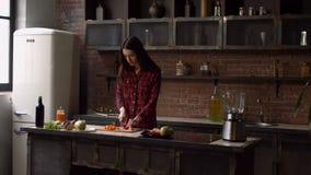 Donna affascinante che taglia carota a pezzi nella cucina video d archivio
