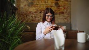 Donna affascinante con belle buone notizie della lettura di sorriso sul telefono cellulare durante il resto in caffetteria, femmi video d archivio
