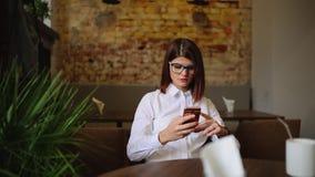 Donna affascinante con belle buone notizie della lettura di sorriso sul telefono cellulare durante il resto in caffetteria, femmi archivi video