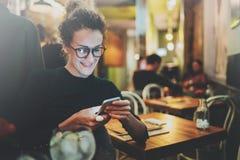 Donna affascinante con il bello messaggio di testo della lettura di sorriso sul telefono cellulare durante il resto in caffetteri Fotografie Stock