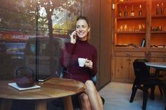 Donna affascinante con il bello sorriso che ha conversazione piacevole sul telefono delle cellule mentre riposando dopo il lavoro Fotografie Stock