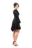Donna affascinante specializzata in vestito nero che guarda giù Vista laterale Fotografia Stock