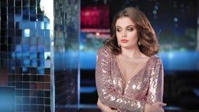 Donna affascinante in vestito di lusso brillante che flirta e che ha buon tempo al fondo al neon della luce della discoteca video d archivio