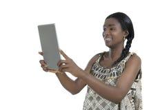Donna africana in abbigliamento tradizionale con il PC della compressa fotografia stock