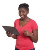Donna africana in camicia rossa che funziona con la compressa Immagini Stock Libere da Diritti