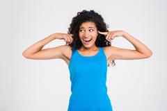 Donna africana che copre le sue orecchie di dito e che grida Fotografia Stock