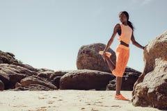 Donna africana che fa allungando allenamento sulla spiaggia Fotografia Stock