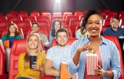 Donna africana che mangia popcorn al cinema fotografie stock