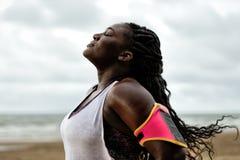 Donna africana che sta sotto la pioggia, occhi chiusi, dopo l'allenamento sulla spiaggia Fotografie Stock Libere da Diritti