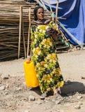 Donna africana che tiene un barilotto dell'acqua su un lookin calmo della strada non asfaltata fotografia stock libera da diritti