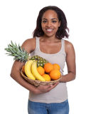 Donna africana che tiene un canestro dei frutti Immagine Stock