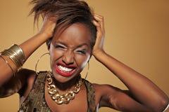 Donna africana che tira i suoi capelli Immagine Stock