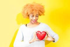 Donna africana con cuore sui precedenti gialli Fotografia Stock Libera da Diritti