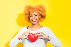 Donna africana con cuore sui precedenti gialli Immagine Stock Libera da Diritti