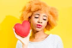 Donna africana con cuore sui precedenti gialli Immagine Stock