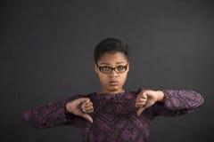 Donna africana con dei pollici il segnale manuale giù sul fondo della lavagna Fotografie Stock