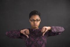 Donna africana con dei pollici il segnale manuale giù sul fondo della lavagna Immagine Stock