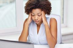 Donna africana con il computer portatile all'ufficio Fotografia Stock