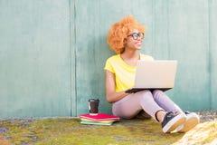 Donna africana con il computer portatile sui precedenti verdi Immagini Stock Libere da Diritti