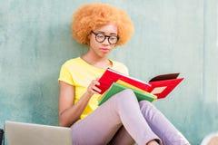 Donna africana con il computer portatile sui precedenti verdi Fotografie Stock