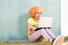 Donna africana con il computer portatile sui precedenti verdi Immagine Stock