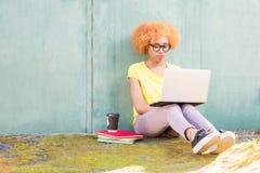 Donna africana con il computer portatile sui precedenti verdi Fotografia Stock