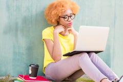 Donna africana con il computer portatile sui precedenti verdi Fotografia Stock Libera da Diritti
