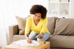 Donna africana con le carte ed il calcolatore a casa Fotografia Stock