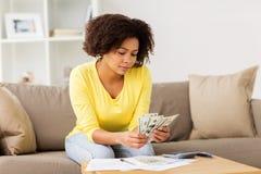 Donna africana con le carte ed il calcolatore a casa fotografia stock libera da diritti