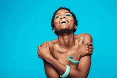 Donna africana con trucco vivo che si abbraccia immagini stock