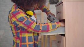 Donna africana con un'acconciatura di afro per mezzo degli strumenti impegnati nel montaggio di mobilia nel salone video d archivio