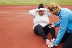 donna africana di Più-dimensione che fa esercizio di sedere-UPS guida dall'istruttore personale Fotografia Stock