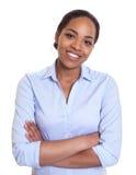 Donna africana di risata in una camicia blu con le armi attraversate Immagine Stock