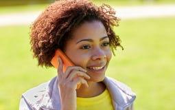 Donna africana felice che rivolge allo smartphone all'aperto Fotografia Stock Libera da Diritti