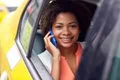 Donna africana felice che rivolge allo smartphone in taxi Immagini Stock